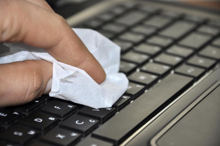 Hand cleaning computer with a cloth.
