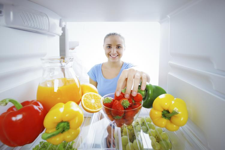 Woman reaching for strawberries in a fridge.