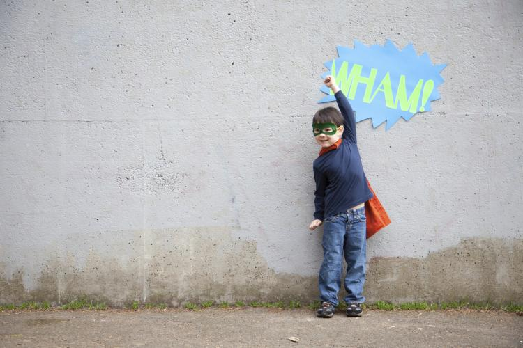 Young boy pretending to be a superhero.