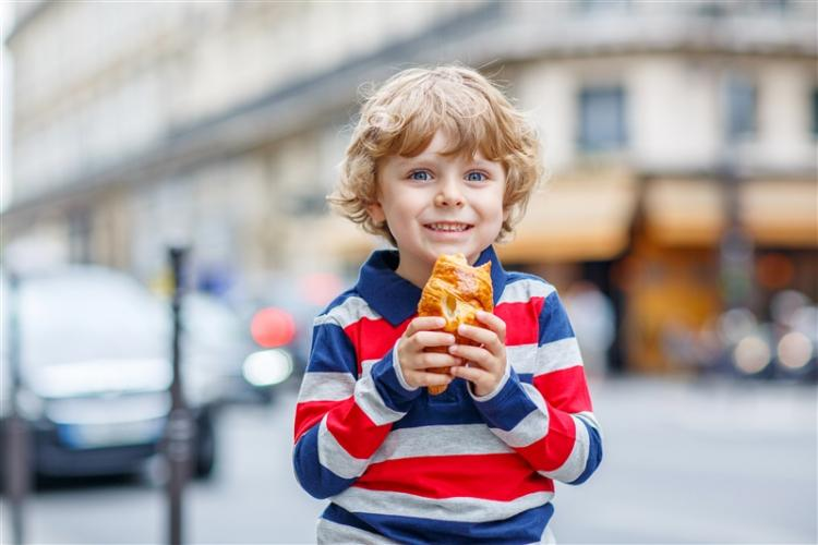 Happy child on street eating a croissant.
