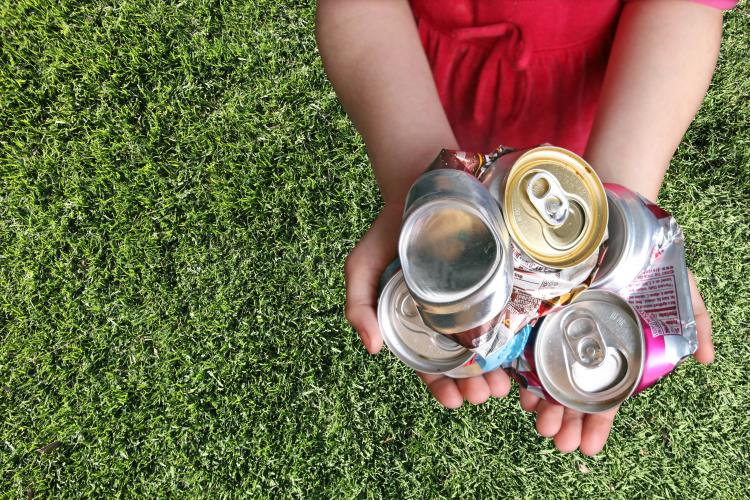 Aluminum cans crushed For recycling in a Child's hands.