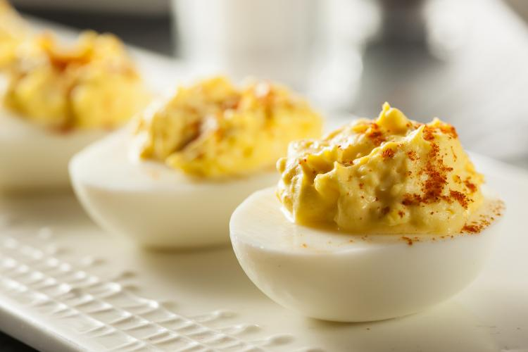 Healthy deviled eggs on a white platter.