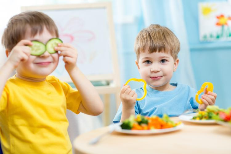 Two boys enjoying their vegetables on Eat Your Vegetables Day.