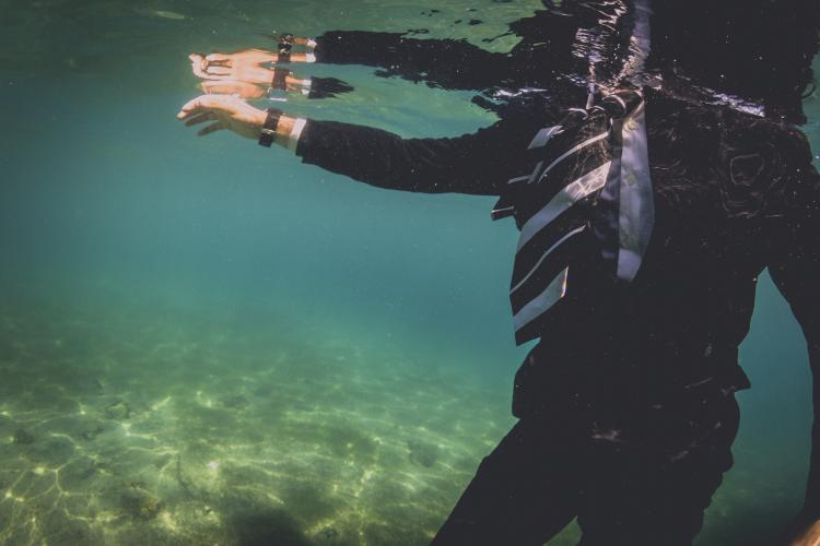 Man in suit under water.
