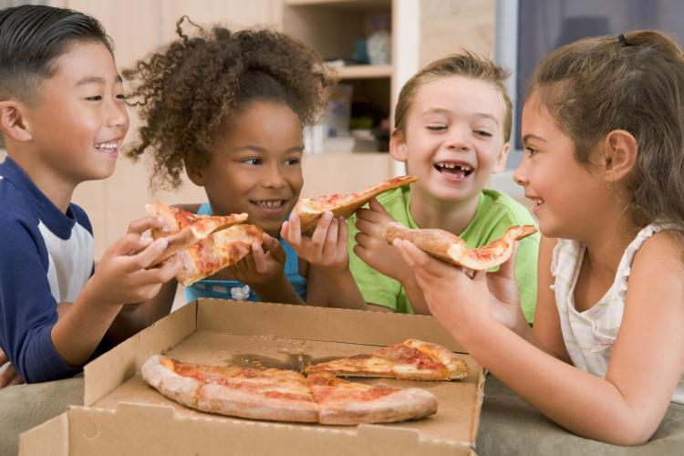 Four young children indoors eating pizza smiling.