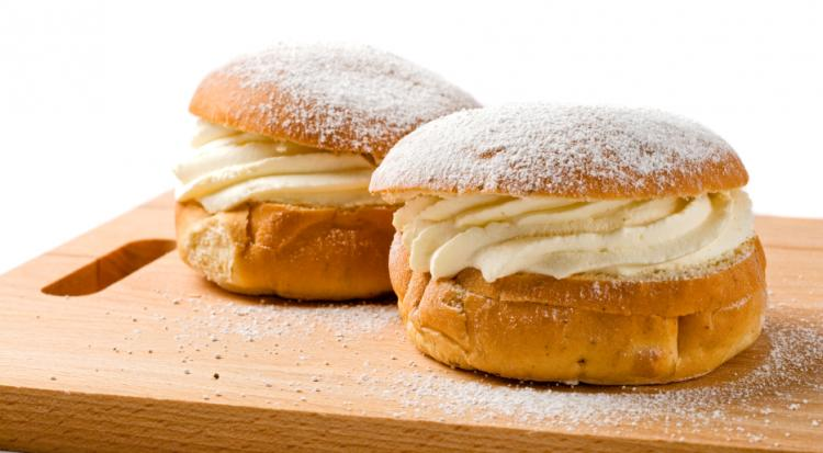 Two wheat buns filled with whipped cream on a plate.