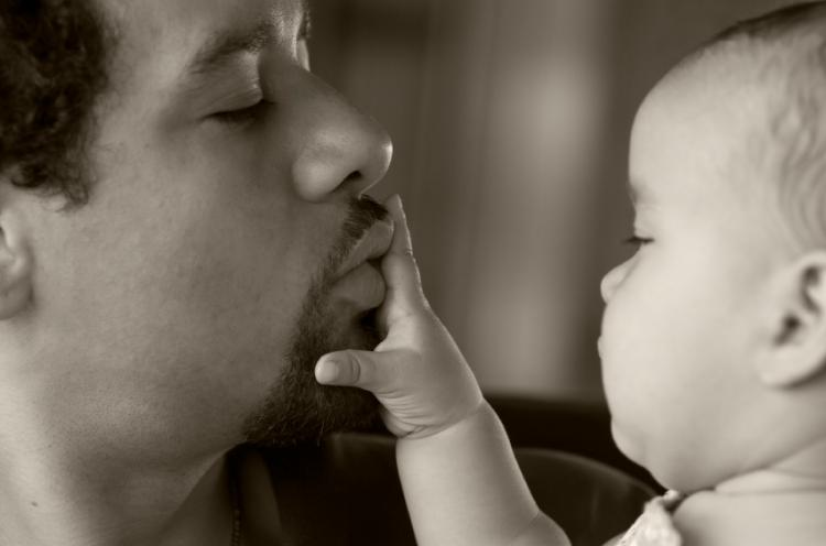 A father lovingly playing with his baby. Black and white image slightly sepia toned.