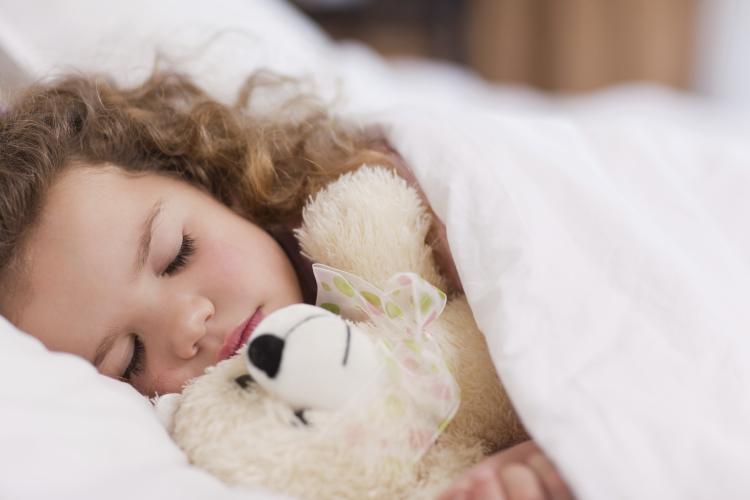 Girl sleeping with her teddy.