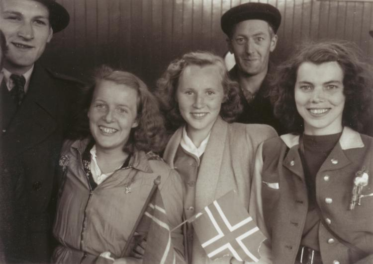 Five smiling young people with Norwegian flags on May 8, 1945.