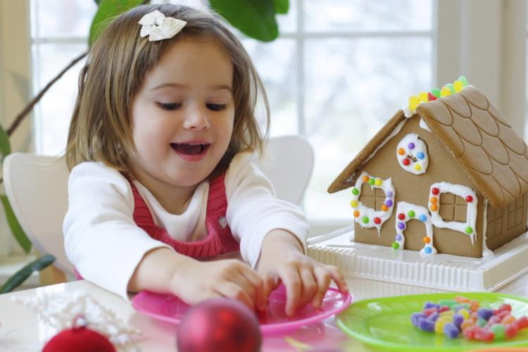 Little girl decorating a gingerbread house.