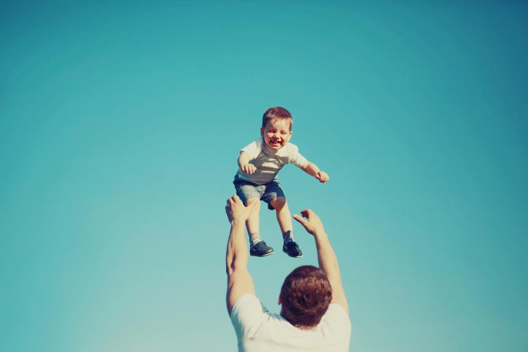 Happy father and child having fun outdoors.