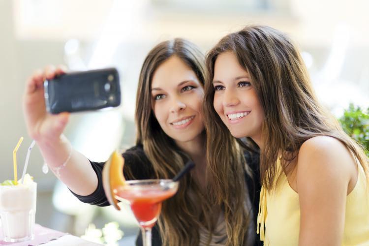 Two girls drinking cocktails and taking a selfie outdoors.