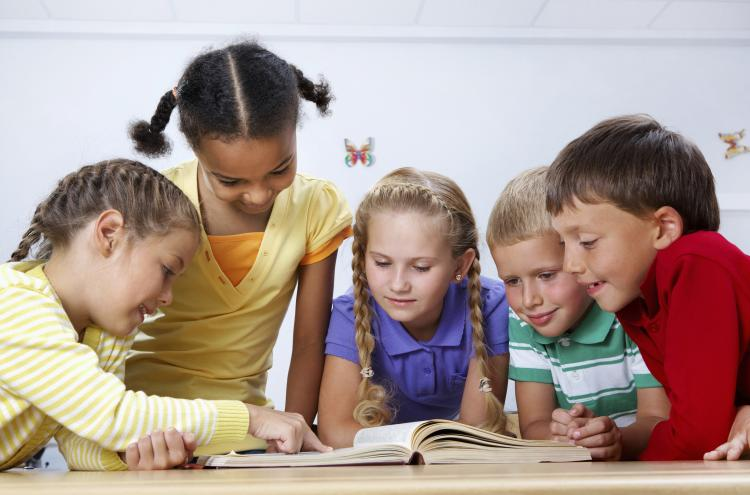 Small group of children reading a book together.