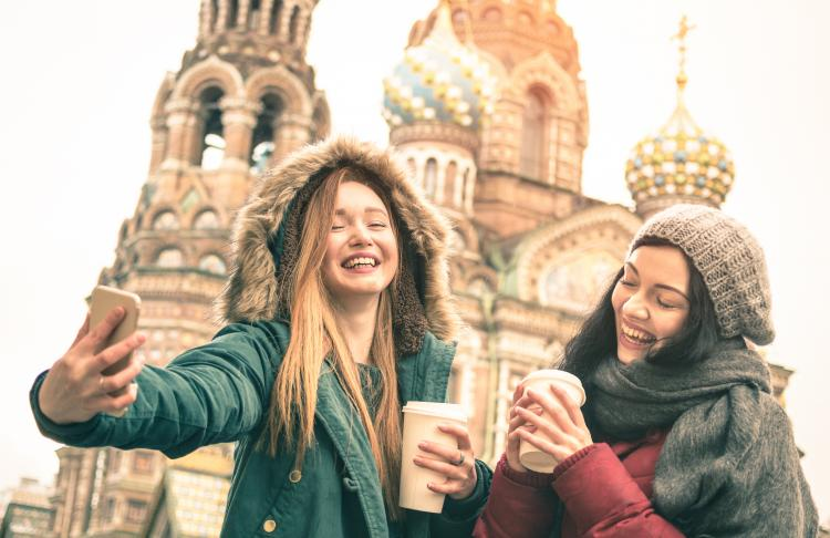 Two smiling girls with coffee cups taking a selfie in Saint Petersburg, Russia.