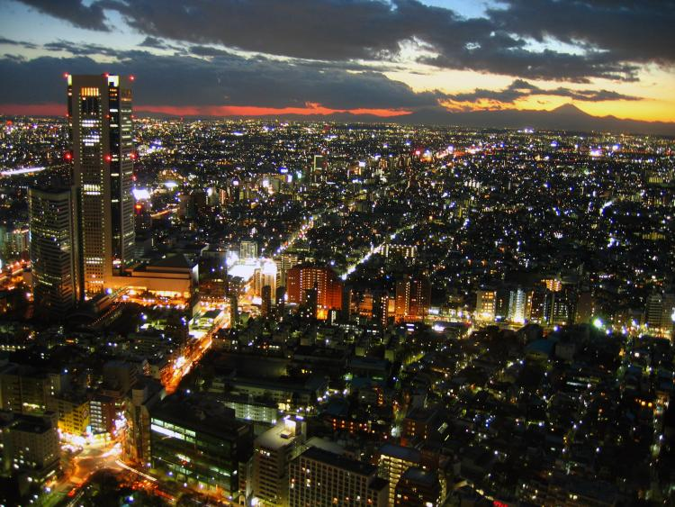 Twilight view over Tokyo metropolis with Mount Fuji on the horizon, back lighten by sun.