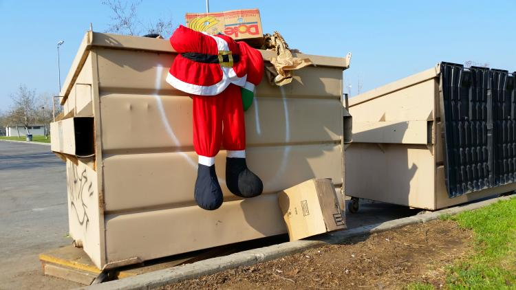 Santa suit discarded in a trash can.