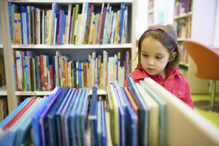 Little girl choosing a book in the library.