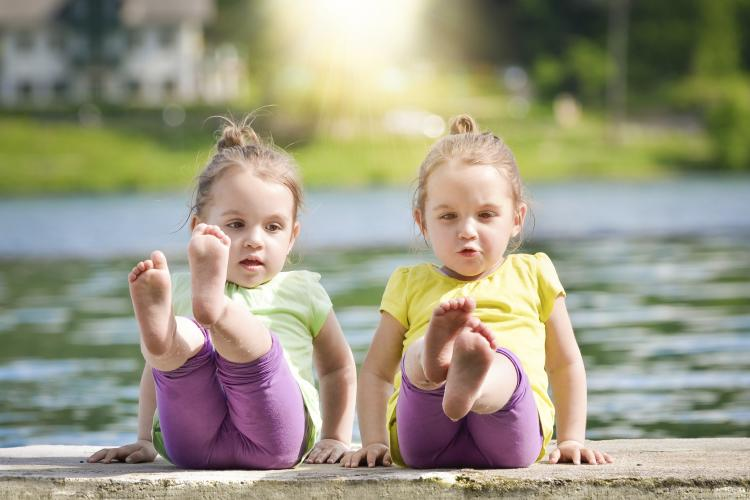 Twin girls exercising on a lake shore.