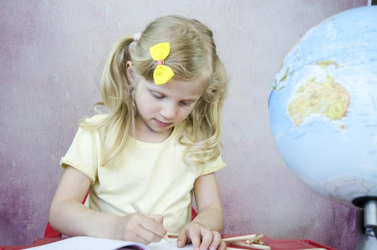 Girl writing on notepad.