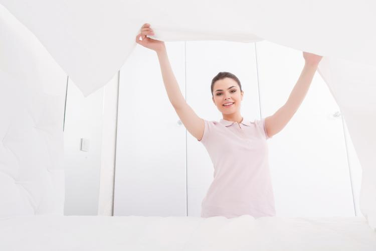 Young female is elegantly making bed in totally white bedroom by lifting blanket.