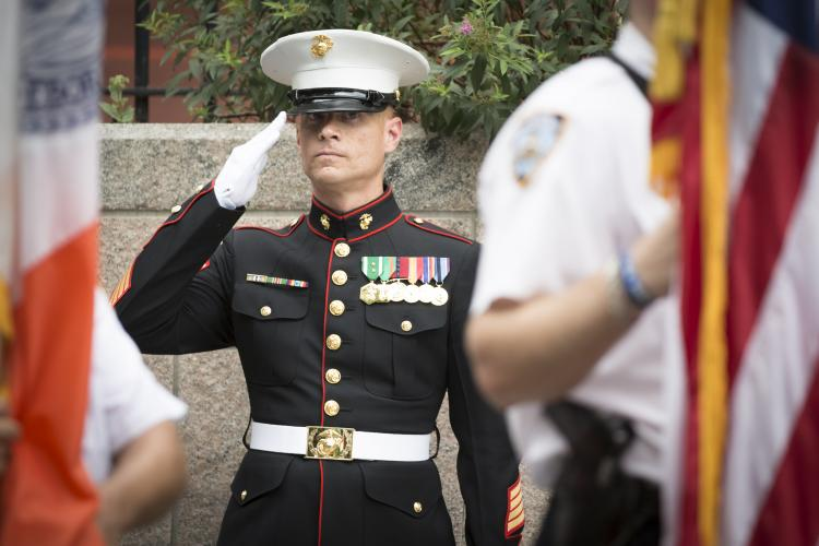 Marine in dress uniform saluting the American flag.