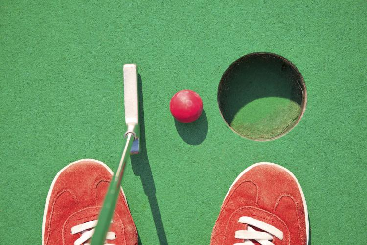 Miniature golf, red shoes and ball near a putting hole.