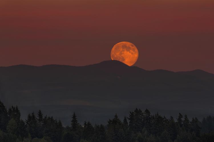 Full Moon rising over Oregon mountain range landscape at dusk.