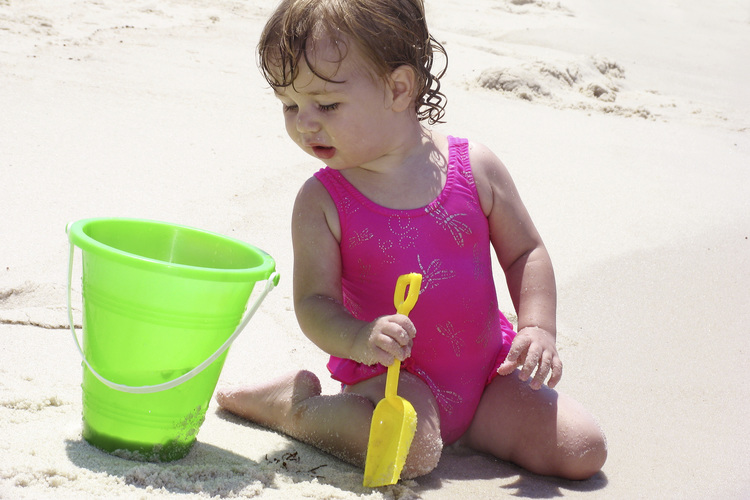 Baby with a bucket on the beach.