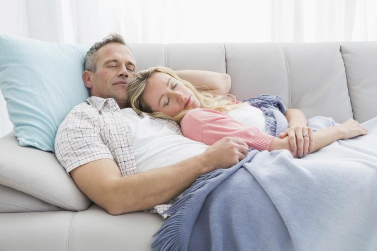 Couple napping under a blanket on the couch.