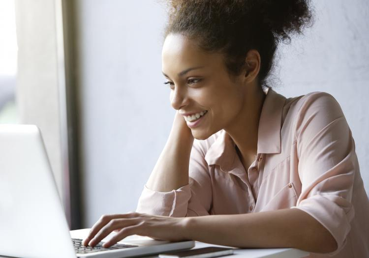 Beautiful young woman smiling and looking at laptop screen.
