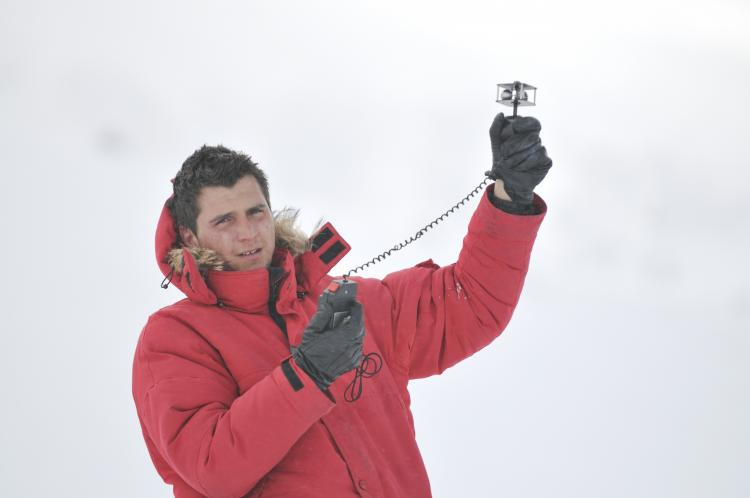 Young weather man measuring wind speed in the winter.