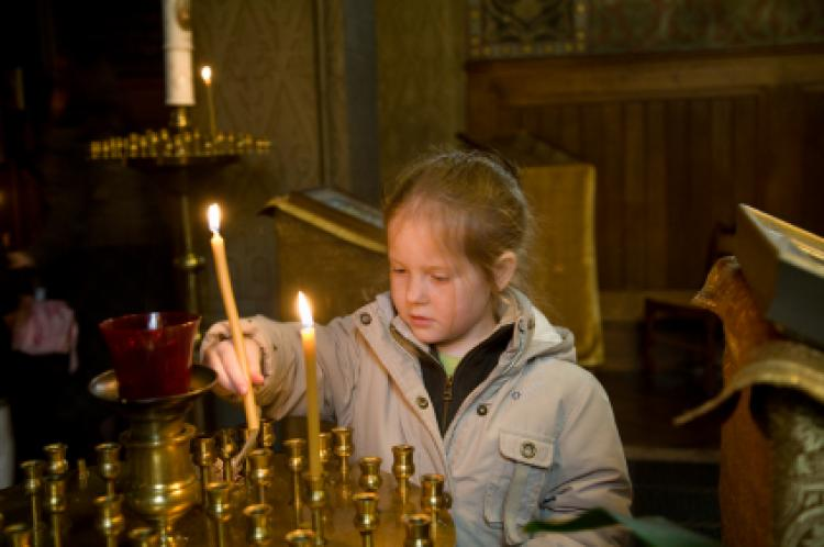 Little Girl light candles in an orthodox church
