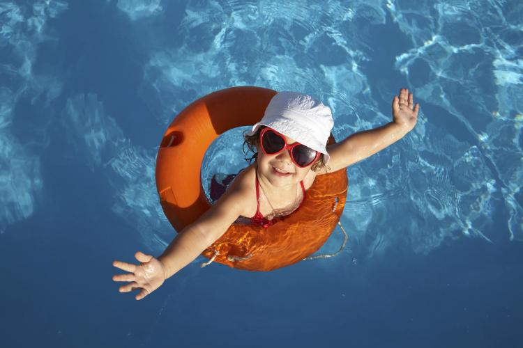 Overhead shot of a young girl in an orange life preserver.