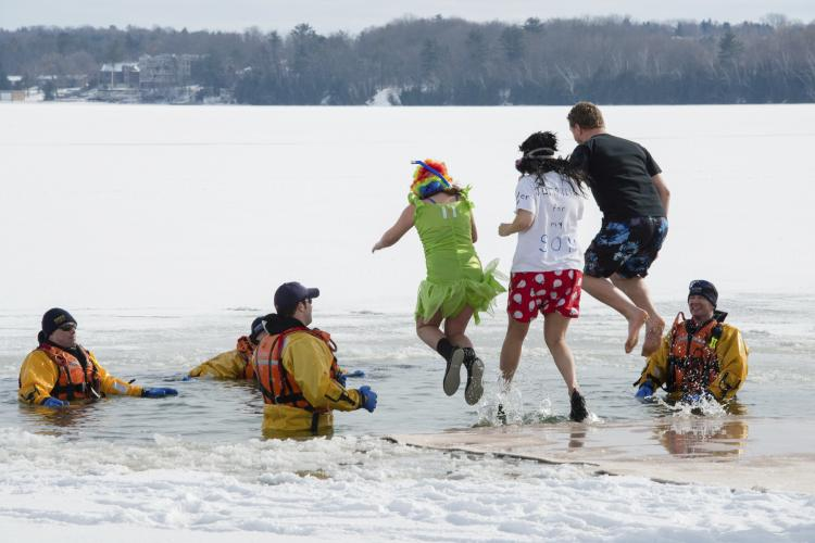 A group of people jump into Kempenfelt Bay during the annual Winterfest's Polar Bear Dip in Barrie, Canada.