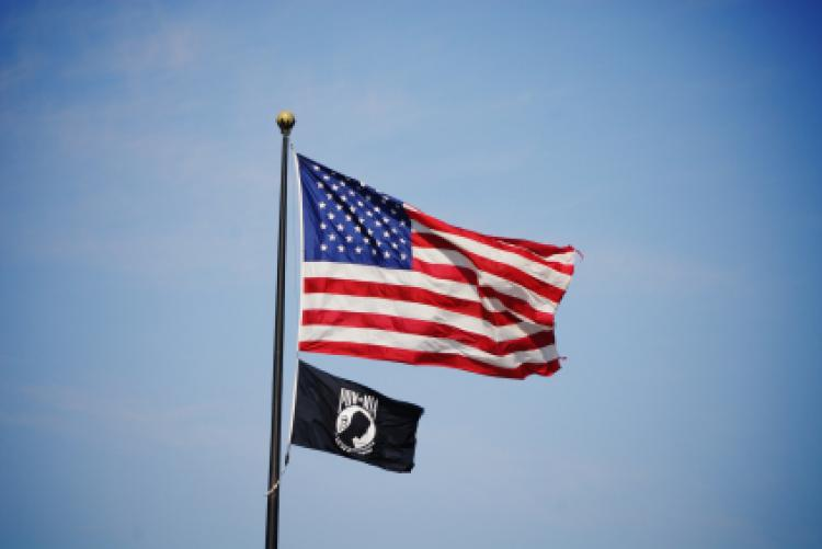 National League of Families' POW/MIA flag is displayed with the United States flag.