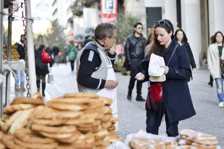 A woman buying from a street vendor in Ermou Street, downtown Athens.