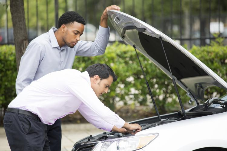 Man helping another man to look at car engine.