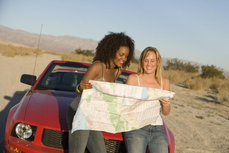 Two women sitting on the hood of a car looking at a roadmap.