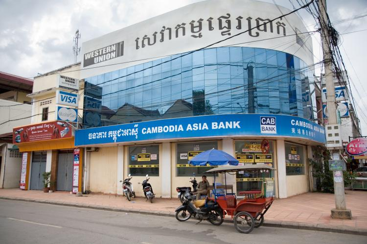 Bank with Western Union sign and tuk-tuk on the street in Siem Reap, Cambodia.