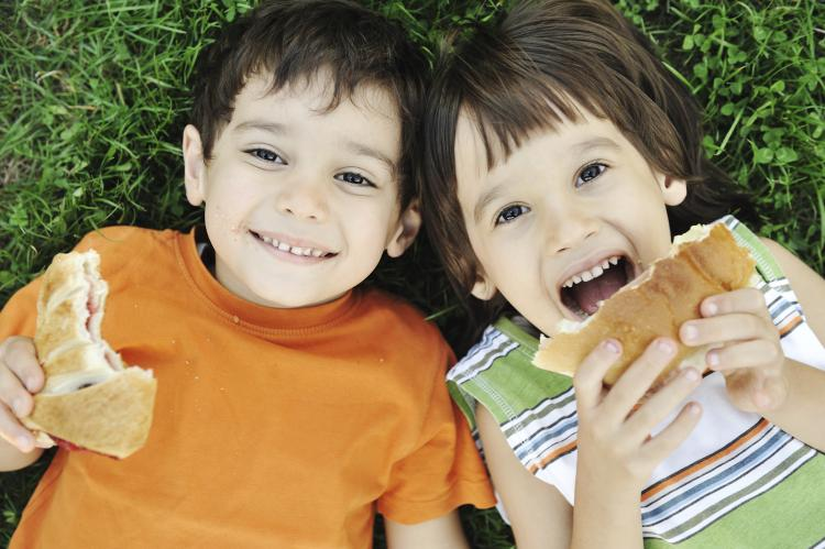 Young kids eating a sandwich.
