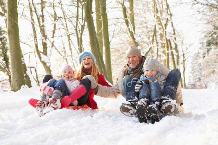 Smiling family sledging in the snow.