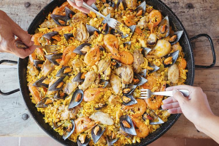 A big pan of mixed paella and forks taking bites from it.