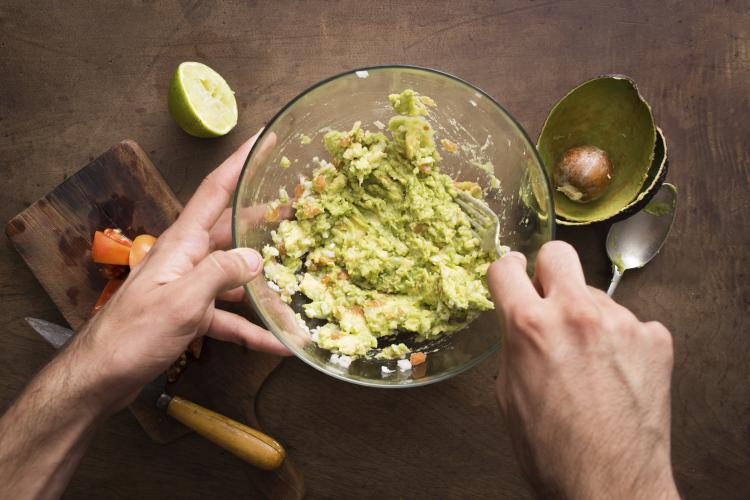 Mashing avocado to make guacamole.