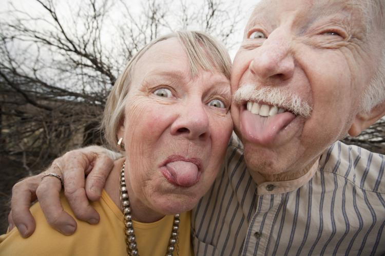 Closeup portrait of an elderly couple outdoors sticking out tongues.