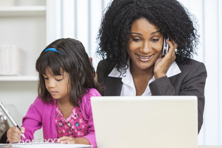 African-American businesswoman at work with a child.