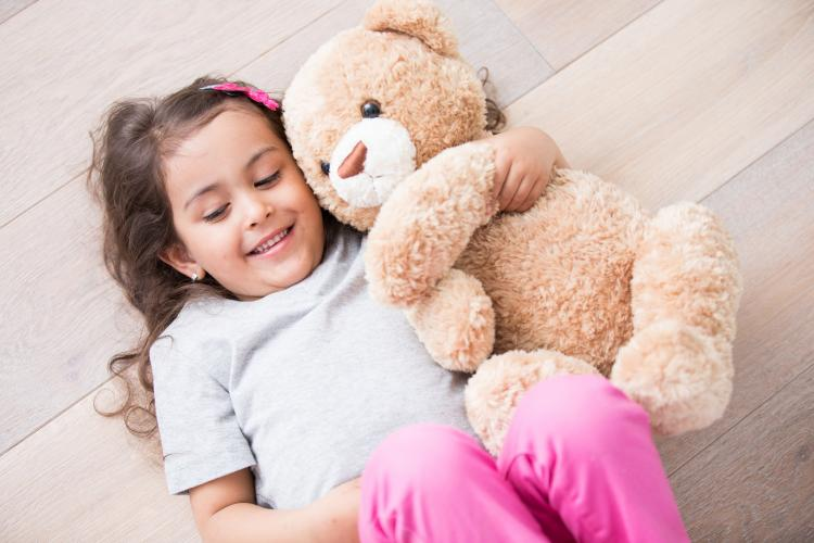Girl with teddy bear lying on wooden floor at home.