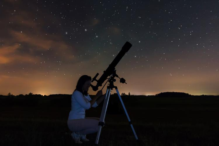 A woman looking at the stars in the night sky through a telescope.