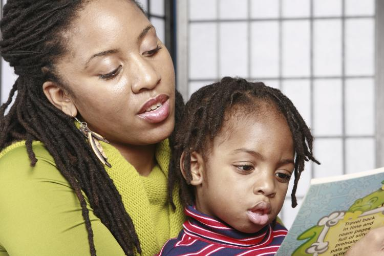 Mum reading a story to her daughter.