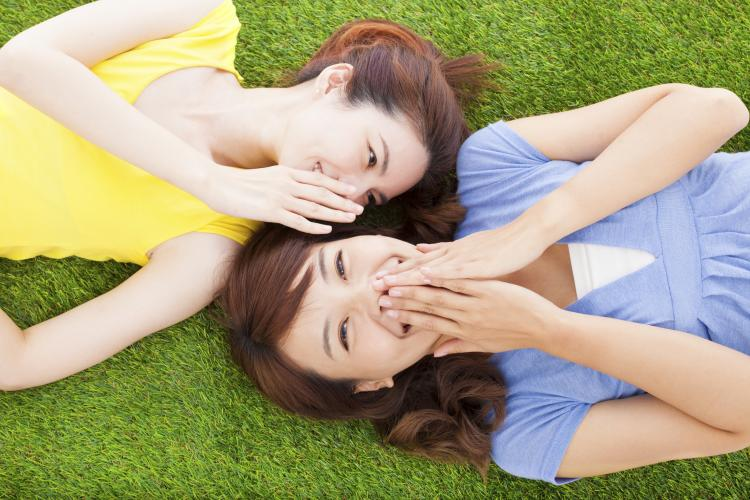 Two sisters whispering to each other while lying on grass.