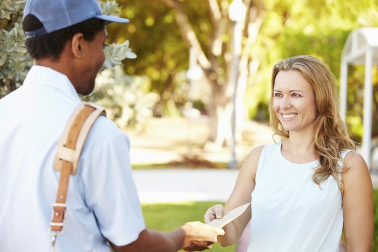 Mailman delivering letters to woman.